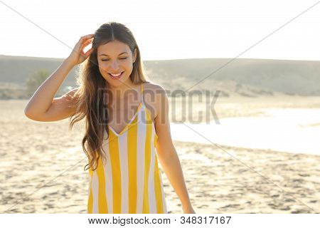 Happy Cheerful Girl In Summer Dress Walking On Sand Beach. Portrait Of Happy Young Woman Smiling At