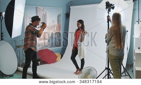 Beautiful African Model Posing For Photo Shoot While Assistant Adjusting The Lighting. Photographer
