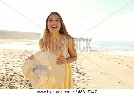 Happy Cheerful Girl In Summer Dress Holding Straw Hat On Tropical Beach. Portrait Of Happy Young Wom