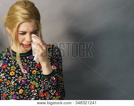 Misery, Infelicity. Blonde Woman Teen Girl About To Cry Wiping Tears Sneezing In A Tissue. Copy Spac