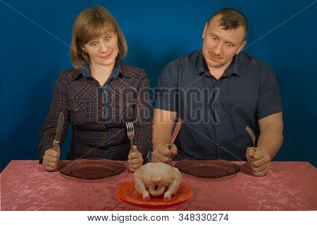 Studio Portrait Of Hungry People On A Blue Background. Want Will Regale On Poultry. Gluttony And Gre