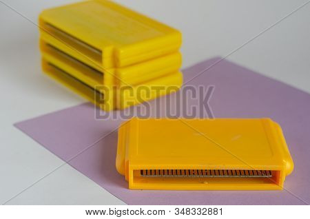 Collection Of Vintage 8 Bit Video Game Cartridges. Yellow Cartridges For Tv Games On A Light Backgro