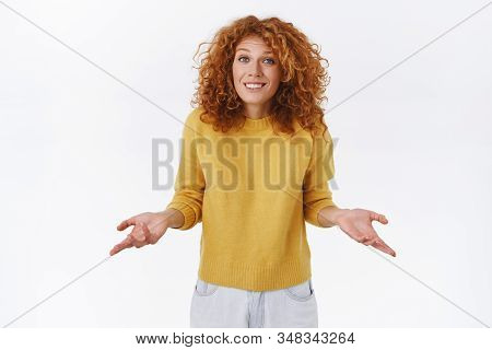 Indesicive, Unsure Cute Young Modern Redhead Curly Woman In Yellow Sweater, Spread Arms Sideways Una