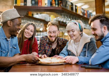 Close Up Happy Diverse Friends Eating Pizza In Cafe Together, Biting Slices, Multiracial People Enjo