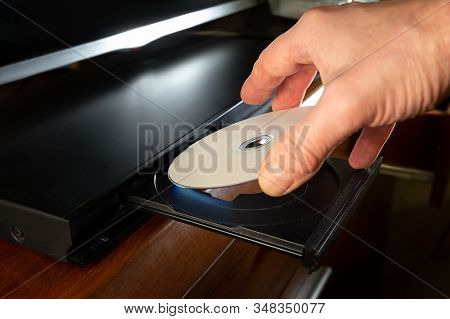 Hand Holding Dvd-disk Insert To Dvd Player