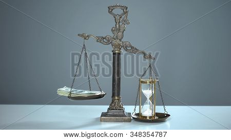 Sandglass outweighs dollars on scales, time is money, valuable resources usage poster