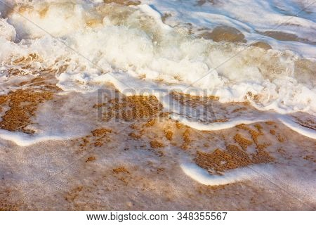 Sea Waves Splash Foam On The Sunny Beach.  Mess Of Salt Water And Sand In Evening Light. Dynamic Nat