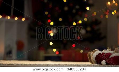 Teddy Bear Toy Lying Near Christmas Tree, Forgotten Winter Holidays In Orphanage