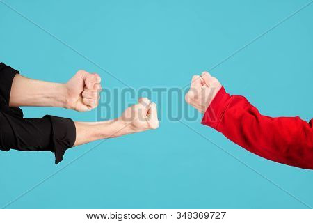 Male Fists Are Directed At Each Other On A Blue Background. The Symbol Of The Fight. Without Face