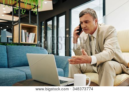 Serious Middle-aged Caucasian Man Wearing Suit Sitting In Front Of Laptop Talking On Phone With His