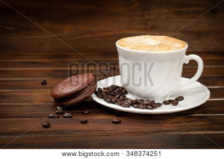 Cappuccino In A White Glass With Saucer. Coffee Beans On A Saucer And On A Brown Background. Nearby