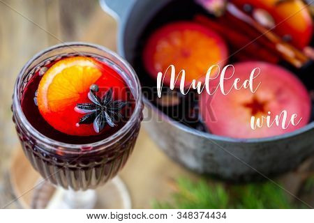 Hot Mulled Wine In A Glass. Beautiful Christmas Drink. Hot Autumn Mulled Wine On A Wooden Table. Del