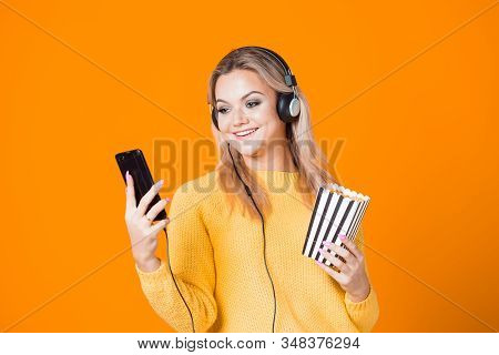 Cinema By Subscription, Concept. A Young Woman In A Yellow Sweater With Headphones With A Smartphone