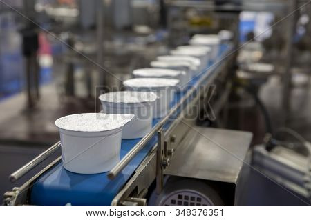 White Yogurt Packages On A Production Line In A Dairy Farm.