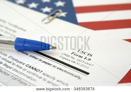 I-9 Employment Eligibility Verification Blank Form Lies On United States Flag With Blue Pen From Dep