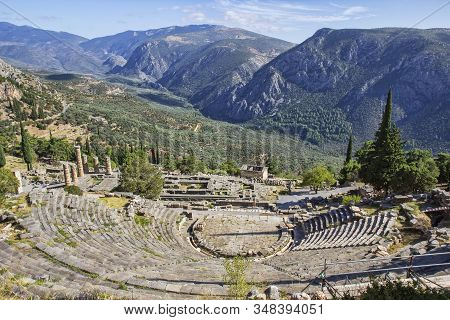 Ruins of the ancient theatre and Temple of Apollo at the archaeological site of Delphi, a UNESCO World Heritage Site, a religious sanctuary dedicated to the Greek god Apollo, on Mount Parnassos, with scenic views of valley below and mountains.