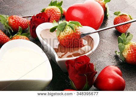 Valentine Chocolate Fondue Melted With Fresh Strawberries And Dark And White Chocolate. Red Roses An