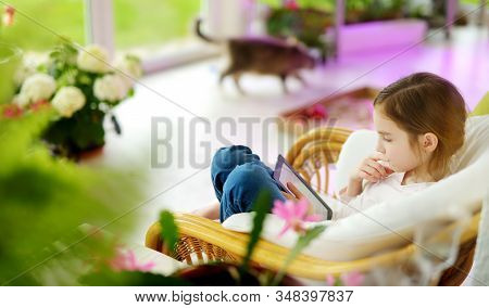 Adorable Little Girl Reading An Ebook In White Living Room On Beautiful Summer Day. Smart Schoolgirl