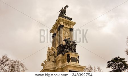Views Of The Statue And Monument To Alfonso Xii In The Parque De El Retiro On A Cloudy Day In Madrid