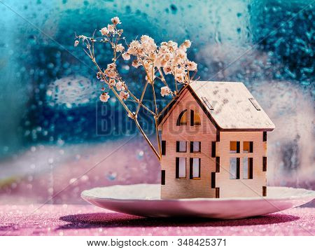 Wooden House Model With A Tree Flowers Against A Rainy Window