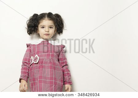 Little Girl With Two Parts Side Pony Hairstyle Looking In Camera With Expression, Childhood Memories