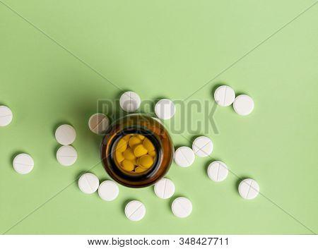Glass And Plastic Drug Bottles With White Pills Inside