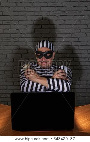 Funny Petty Crook In Exaggerated Prisoners Clothes And A Black Mask With A Silly Face Steals Money O
