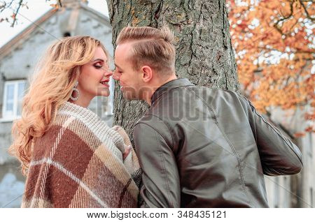 Young Couple Kisses Outdoors By The Tree, Autumn Love Story Concept