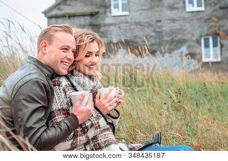Young Couple In Love With A Hot Drink In Their Hands Dreams Of A Joint Future Outdoors