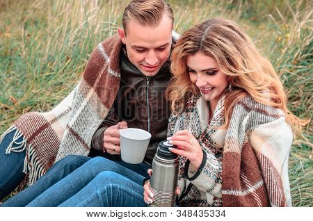 Young Couple In Love Drink Tea From A Thermos Outdoors On A Cold Autumn Day, Concept Of Romantic Lov