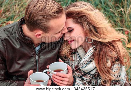 Happy Couple In Love Outdoors Warm Up With Tea On A Cold Autumn Day, Guy Kisses A Girl