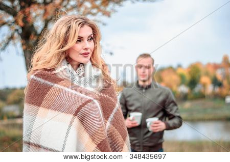 A Guy Treats A Cup Of Hot Tea To His Girlfriend Who Froze In Cold Autumn Weather And Wrapped Herself