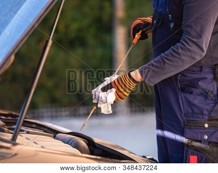 Hand Of Car Mechanic Check Engine Oil For Maintenance .