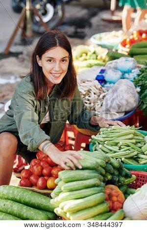 Portrait Of Cheerful Caucasian Woman Choosing Fresh Vegetables At Farmers Market Looking At Camera S