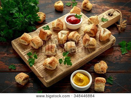 Pork Sausage Rolls With Mustard And Ketchup Sauce On Wooden Board