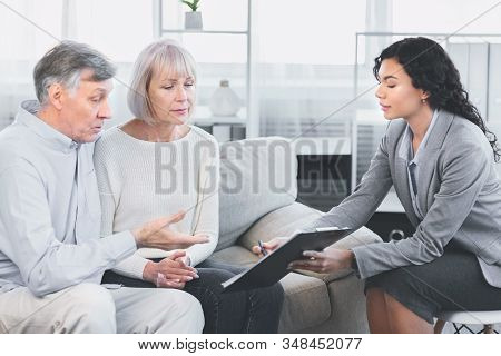 Last Will And Testament. Mature Man Sitting On Couch Embracing Wife, Asking About Document, Signing