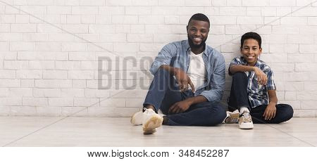 Like Father Like Son. Preteen Black Boy Sitting On Floor In Similar Pose With His Dad Near White Bri