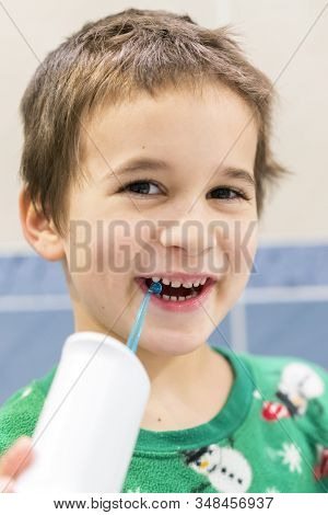 A 5-year-old Boy At Home Washes His Teeth With An Oral Irrigator. Little Boy Cleaning Teeth With Ora