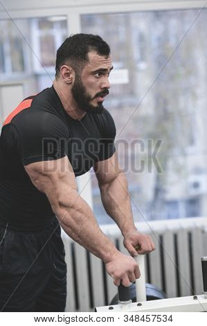 Handsome Young Bearded Man In Black Jersey Rest In Gym During Hard Workout Training Pause