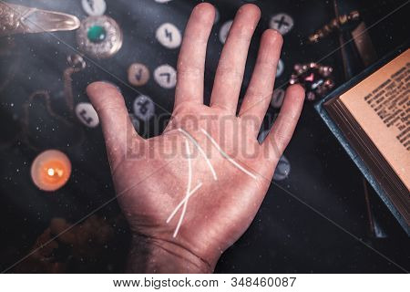 Astrology And Esotericism. Male Palm Close-up With White Lines. On A Black Background Lie Runes, A C