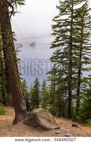 View Of Phantom Ship Island In The Mist And Trees On A Stormy Day By Crater Lake, Oregon, Usa