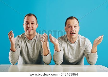 Identical Twin Brothers Surprised With Something Sitting At Table Looking At Camera, Horizontal Shot