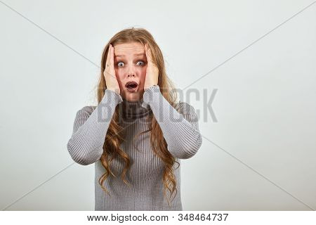 A Young Beautiful Red-haired Woman In Gray Sweater Holds Her Head With Her Hands From Surprise Frigh