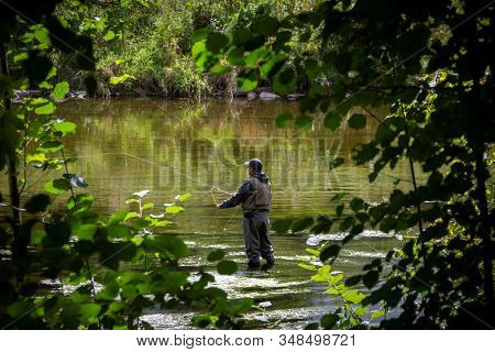 A Portrait Of A Fisher Man Fishing In A River Hoping To Catch Some Kind Of Fish. The Fisher Man Is W