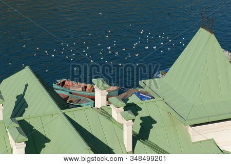 Scenery Sea Bay With Boats And Seagulls With Green Tinny Roof On Foreground