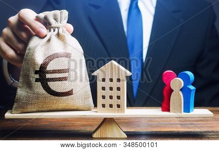 Man Puts Euro Money Bag And House On Scales With A Family. Mortgage, Debt Burden. Assistance With Ho