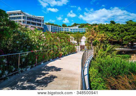 Beautiful Beach Resort With Flowery Walkway And Modern Buildings. Beach Hotels And Oleander Flowers
