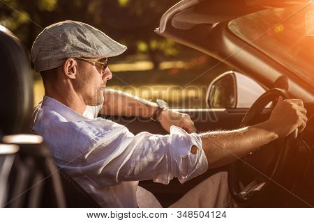 Summer Time Road Trip In His Cabrio Car. Caucasian Men In Driving Convertible Vehicle
