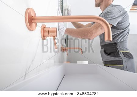 New Bathroom Finish Cleaning. Copper Color Elegant And Stylish Faucet And White Ceramic Sink. Bathro