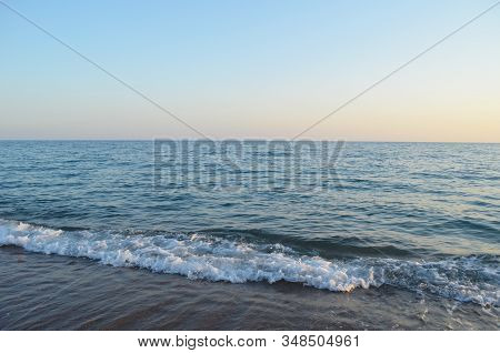 Mediterranean Sea At Sunset. Waves Break On The Sandy Shore, Sea Foam. Natural